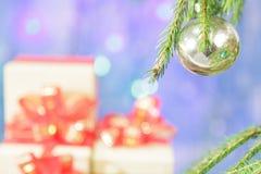 Ein Weihnachtsbaumast wird mit einem Weihnachtsball verziert Lizenzfreie Stockbilder