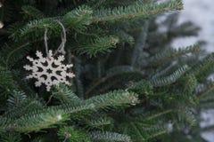 Ein Weihnachtshintergrund der Tanne ein Baum mit einer hölzernen Schneeflocke Lizenzfreies Stockfoto
