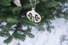 Ein Weihnachtshintergrund der Tanne ein Baum und ein hölzerner Ball Stockbilder