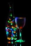 Ein Weinglas und eine Flasche der beleuchteten Girlande Stockfotos
