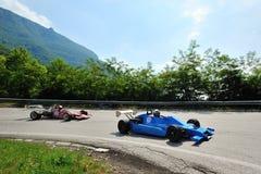 Ein Weinlese F3-Auto, das von einer roten Formel Ford gefolgt wird, nimmt zum Rennen Kirchenschiff Caino Sant'Eusebio teil Stockbilder