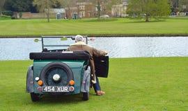 Ein Weinlese-Morris Minor-Automobil parkte nahe Wasser mit Fahrer Lizenzfreies Stockfoto