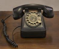 Ein Weinlesedrehskalatelefon auf einem alten Holztisch lizenzfreies stockbild