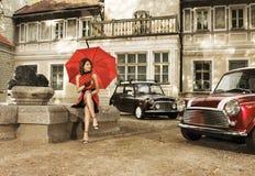 Ein Weinlesefoto einer jungen Frau mit einem Regenschirm Stockfotografie