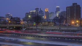 Ein Weitwinkelschuß des Autobahnverkehrs vor im Stadtzentrum gelegenem Minneapolis während einer düsteren Winter-Dämmerung stock footage