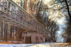 Ein Winterfoto einer metallischen Struktur, die verschiedene Rohre auf den Betonblöcken laufen durch einen Wald mit dem Sonnenglä Stockfotografie