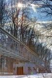 Ein Winterfoto einer metallischen Struktur, die verschiedene Rohre auf den Betonblöcken laufen durch einen Wald mit dem Sonnenglä Lizenzfreies Stockbild