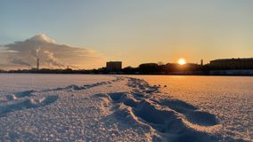 Ein Winterstadtüberblick Gefrorener Fluss bedeckt im Schnee Sonnenuntergang Füße Spuren stock video