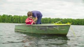 Ein Wissenschaftler, der die Tiefe des Sees unter Verwendung eines speziellen Gerätes misst stock footage
