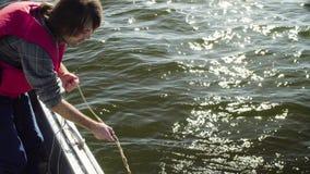 Ein Wissenschaftler lässt ein anziehendes Gerät des Planktons in das Wasser fallen stock footage