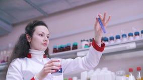 Ein Wissenschaftler schätzt Flüssigkeit in einem Reagenzglas stock footage