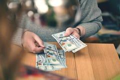 Ein wohlhabender Mann zählt Dollar Hände und 100 Dollarscheine schließen oben Stockfotografie