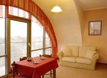 Ein Wohnzimmerinnenfragment mit einem roten lambrequin an einem Fenster und ein Bild auf einer Wand Stockfoto