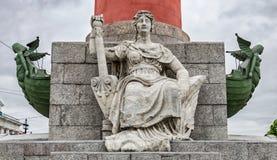 Ein woman& x27; s-Zahl mit zwei Podien, die am Fuß der Podiumsspalte auf dem Spucken von Vasilievsky-Insel sitzen Stockfotos