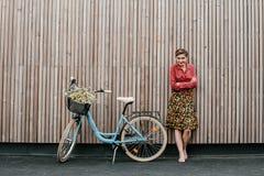 Ein wunderbares M?dchen reist mit dem Fahrrad Gehen in das Freien Sch?nheit mit einem Korb von Blumen Fahrradfahrt stockfoto