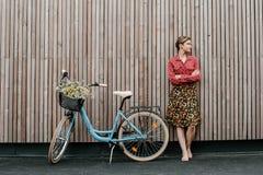 Ein wunderbares M?dchen reist mit dem Fahrrad Gehen in das Freien Sch?nheit mit einem Korb von Blumen Fahrradfahrt stockfotos
