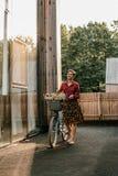 Ein wunderbares M?dchen reist mit dem Fahrrad Gehen in das Freien Sch?nheit mit einem Korb von Blumen Fahrradfahrt lizenzfreie stockfotografie