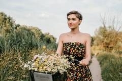 Ein wunderbares M?dchen reist mit dem Fahrrad Gehen in das Freien Sch?nheit mit einem Korb von Blumen Fahrradfahrt stockfotografie