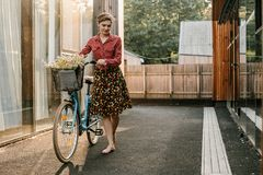 Ein wunderbares M?dchen reist mit dem Fahrrad Gehen in das Freien Sch?nheit mit einem Korb von Blumen Fahrradfahrt lizenzfreies stockbild