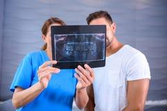 Ein Zahnarzt, der die Ergebnisse eines RÖNTGENSTRAHLS dem Patienten erklärt Lizenzfreie Stockbilder