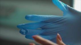 Ein Zahnarzt tr?gt blaue Gummihandschuhe Blaue Handschuhe kleiden Doktor H?bscher junger Doktor, der auf Gummihandschuhe ins Kran stock video