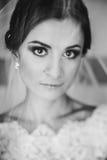 Ein zartes Bild einer Braut, die unter einem Schleier steht Stockbild