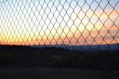Ein Zaun, der einen Sonnenuntergang zeigt Stockbild