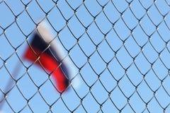 Ein Zaun hinter dem des Metalldrahts die russische Flagge Lizenzfreie Stockfotos