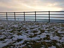Ein Zaun und ein Schnee auf dem Gras lizenzfreie stockbilder