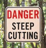 Ein Zeichen der Warnung in Richtung zum tiefen Ausschnitt, der innerhalb des Weges voran ist. lizenzfreies stockfoto