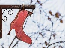 Ein Zeichen in Form eines roten weiblichen Stiefels des alten Eisens mit einer scharfen Ferse auf einem unscharfen weißen Hinterg stockfotografie