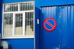 Ein Zeichen, welches das Parken von Autos auf einer blauen Wand und weiße wi verbietet Lizenzfreies Stockbild