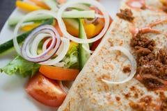 Ein Zerkleinerungspfannkuchen mit Salat auf der Seite Lizenzfreie Stockbilder