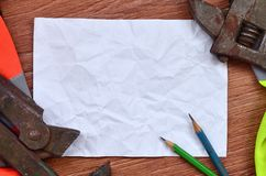 Ein zerknittertes Blatt Papier mit zwei Bleistiften umgeben durch die grünen und orange Arbeitsuniformen und die justierbaren Sch Stockbilder