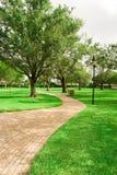 Ein Ziegelsteinpfad im Park lang Lizenzfreies Stockbild