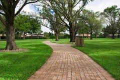 Ein Ziegelsteinpfad im Park lang Lizenzfreies Stockfoto