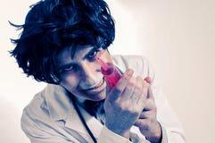 Ein Zombiedoktor mit einer Spritze mit Blut, mit einem Filtereffekt Lizenzfreie Stockfotografie