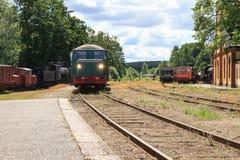 Ein Zug, der in die alte Bahnstation auf dem Seeufer in Nora Sweden zieht Lizenzfreies Stockbild