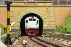 Ein Zug kommt heraus ein geometrischer Tunnel stockfotografie