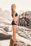 Ein zusammengesetztes Bild der blonden Stellung des Sitzes auf dem Strand auf einem Felsen Lizenzfreie Stockbilder