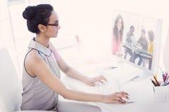 Ein zusammengesetztes Bild des lächelnden Designers, der Tablette verwendet Lizenzfreies Stockfoto