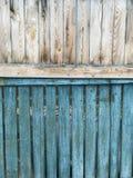 Ein zweifarbiger Bretterzaun - die Spitze ist beige und die Unterseite ist blau lizenzfreies stockfoto