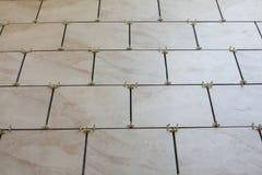 Einbau der Fußbodenfliesen und -distanzscheiben Stockbilder