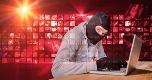 Einbrecher, der auf Laptop vor rotem digitalem Schirm schreibt Stockbilder