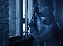 Einbrecher, der in ein Haus einbricht Stockfoto