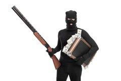 Einbrecher, der eine Tasche voll vom Geld und von einem Gewehr hält Lizenzfreie Stockfotos
