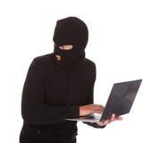Einbrecher, der Laptop verwendet Stockbild