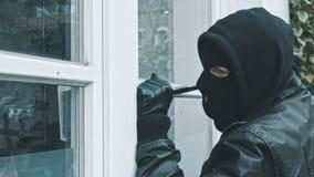 Einbrecher mit der Brechstangenbruchtür, zum des Hauses zu betreten stock footage