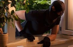 Einbrecher späht in das Haus Stockbilder