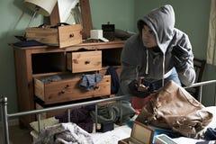 Einbrecher-Stealing Items From-Schlafzimmer während des Haus-Bruches herein Stockbilder